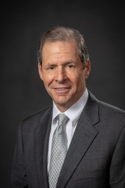 Headshot of Dr. Howard B. Fleishon with dark gray background